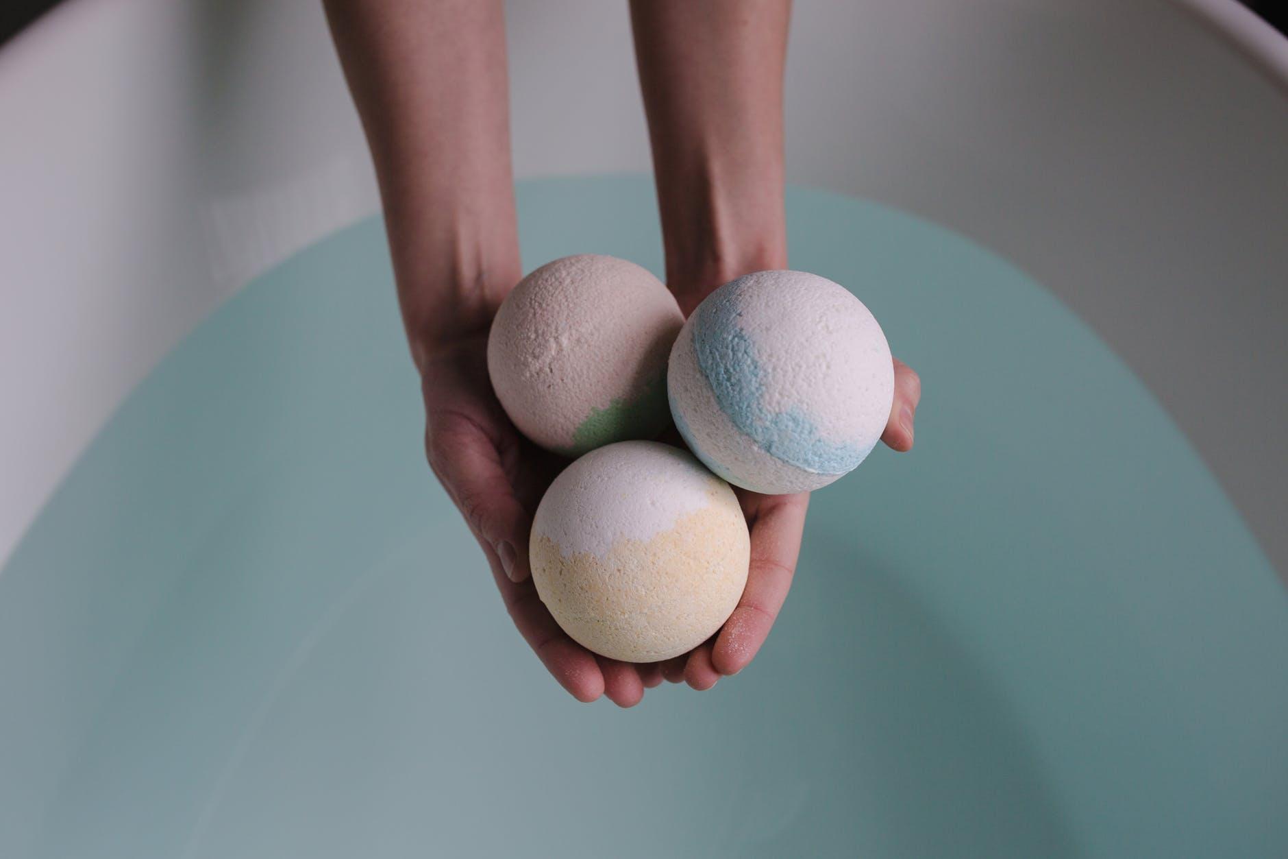 person holding three bath balls